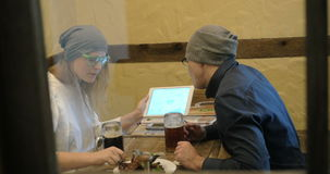 Young people having nice evening with beer and pad. Young hipster man and woman enjoying evening in cafe. They drinking beer with tasty toasts and having a talk stock video