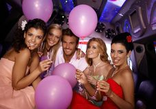 Young people having party in limo. Attractive young people having party in limousine Stock Photography