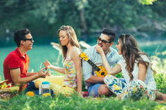 Young people having picnic near the river. Stock Photos