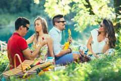 Young people having picnic near the river. Stock Photo