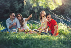 Young people having picnic near the river. Stock Images