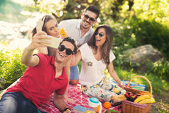 Young people having picnic near the river. Young friends relaxing by the river Stock Photography