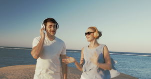 Young people in headphones relaxing on beach. Steadicam shot of young man and woman in wireless headphones walking on the beach. They singing and dancing with stock video