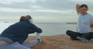 Young people in headphones working out by the sea. Steadicam shot of young couple having workout on the beach by the sea. They doing exercises while listening to stock footage