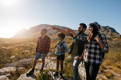 Young people hiking on extreme terrain. Group of friends on hike pointing away at a view. Young people hiking on extreme terrain on a summer day Royalty Free Stock Images