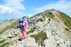 Young People Hiking up on Rocky Mountain Slope Royalty Free Stock Photos