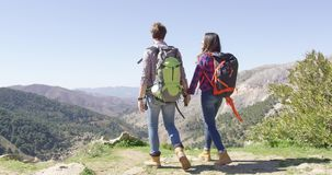 Young people holding hands. Back view of young couple with backpack holding hands and enjoying view of mountains in summer time stock footage