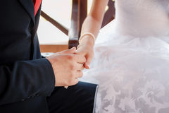 Young people holding hands while sitting on a bench in the park. Wedding Stock Images