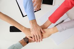 Young people holding hands together over table, top view. royalty free stock image