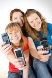 Young people holding mobiles. Smiling young woman with teenage friends holding mobile telephones, studio background Royalty Free Stock Images