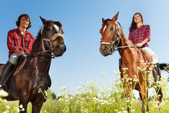 Young people horseback riding in flowery meadows Royalty Free Stock Photography