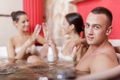Young people in the hot tub. Young people enjoying themselves in the hot tub Royalty Free Stock Photo