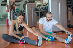 Young people involved in sports. Woman stretching with personal trainer Stock Photo