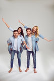 Young people in jeans. Two beautiful young couples in jeans are looking at camera and smiling, standing barefoot on a gray background. Girls pickaback Royalty Free Stock Image