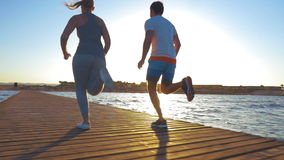 Young people jogging on the pier at sunset. Slow motion steadicam and low angle shot of man and woman running on wooden pier on coastal resort at sunset stock video footage