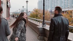 Young people joyfully walk in the city, two of them dance a bit, smile and have fun. Slow mo, steadicam shot, back view. Four stylish people cheerfully walk in stock video footage