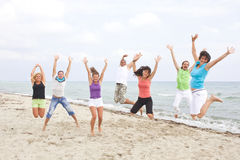 Young people jumping on the beach Stock Images
