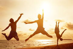 Young people jumping on the beach with sunset Royalty Free Stock Image