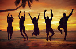 Young People Jumping with Excitement on the Beach Royalty Free Stock Photo