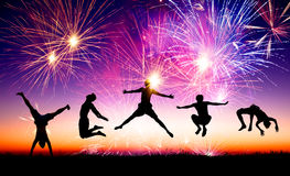 Young people jumping on the hill with firework background Royalty Free Stock Photo