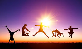 Young people jumping on the hill with sunlight background. Happy young people jumping on the hill with sunlight background Royalty Free Stock Images