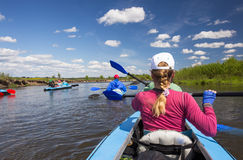 Young people are kayaking on a river in beautiful nature. Summer sunny day Royalty Free Stock Photography