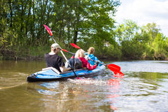 Young people are kayaking on a river in beautiful nature. Summer sunny day Stock Image