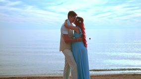 Young people kissing on sea beach. Pregnant couple kissing. Happy couple beach. Young couple kissing on sea beach. Romantic vacation. Red hair woman with stock footage