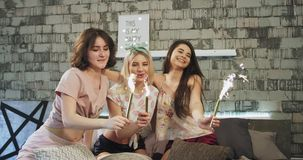 Young people ladies using a sparkling fireworks at their home pajamas party smiling , they enjoy the time together in a stock footage