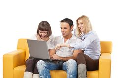Young people with laptop. Three amused people with laptop computer sit on yellow sofa royalty free stock photography