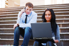 Young business couple using laptop outdoor Royalty Free Stock Image