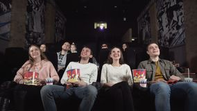 Young people laugh at comedy movie in cinema theatre. Young people laughing at cinema watching amusing comedy. stock video footage