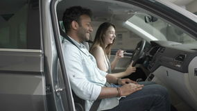 Young people laughing in car`s cabin. Young people sits inside the automobile. Young woman and swarthy man are laughing. The people fasten the belts. Happy guy stock video footage