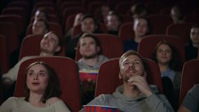 Young people laughing at cinema theater. Young people watching amusing comedy. Young people laughing at cinema theater. Joyful people watching amusing comedy stock video