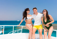 Young people laughing and standing on the yacht at a sunny summe Stock Image