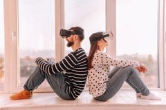 Young people leaning with their backs to each other. Always together. Young pleasant people leaning with their backs to each other using virtual reality devices royalty free stock image