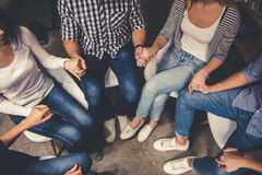 Young people in the library. Young people are sitting in circle and holding hands while having a meeting in the modern library Royalty Free Stock Photo