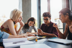 Young people in library working on school assignment Royalty Free Stock Photo