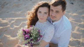 Young people in light clothes sit on the sand. Young loving couple sit on the sand and look at the camera.Wind play in their hair.Lady hold bouquet of stock video footage