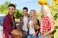 Young people listening guy playing guitar friends drinking beer bottles outdoor countryside Royalty Free Stock Photos