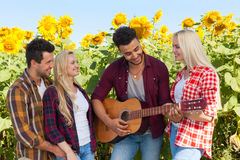 Young people listening guy playing guitar friends drinking beer bottles outdoor countryside Stock Photo