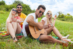 Young people listening guy playing guitar group friends summer day Royalty Free Stock Image