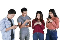 Young people look busy with phones on studio royalty free stock photos