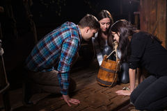 Young people looking in the bucket in search of conundrum soluti. On to get out of the trap, escape the room game concept Stock Photography