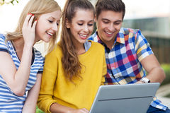Young people looking at laptop together. Portrait of young people outdoors Stock Photography