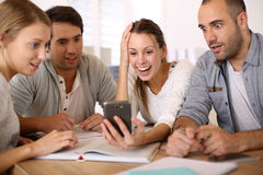 Young people looking at smartphone being shocked Royalty Free Stock Photography