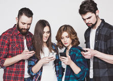 Young people looking at their phones stock photos
