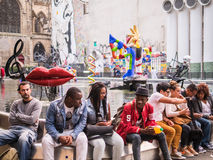 Young people lounge and talk on the wall surrounding the Fontain Stock Photos