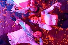 Young People Lying in Confetti. Top view of three young people lying on floor among confetti and serpentine and smiling looking at camera during awesome house Stock Image