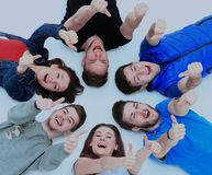 Young people lying down. Gesturing thumb up sign Royalty Free Stock Photos